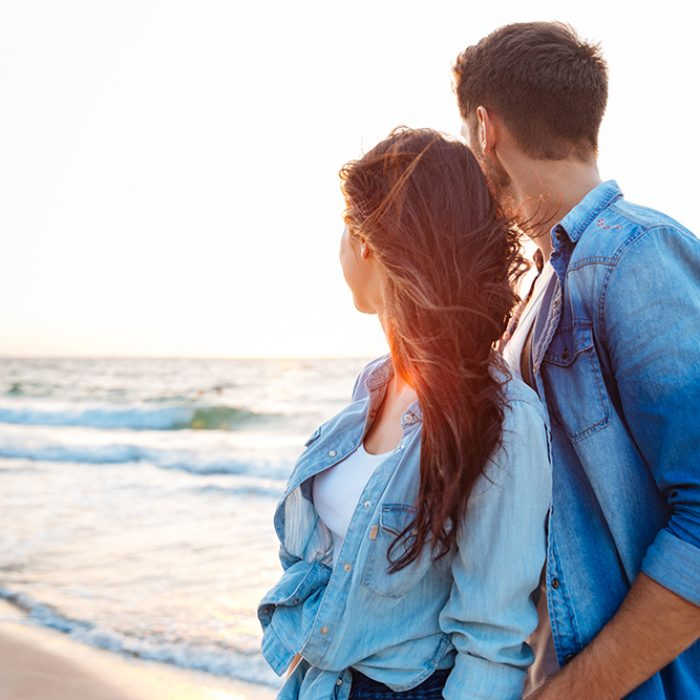 Beautiful young couple looking at sunrise on the beach